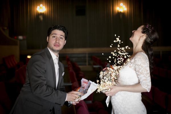 Brautpaar wirft  im Kino mit Popcorn