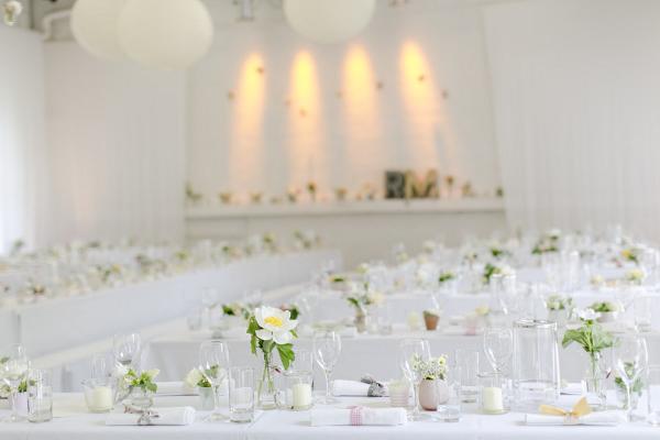 Gartenhochzeit in weiß: dekorierter Saal in der Orangerie in Köln. Foto: Hanna Witte