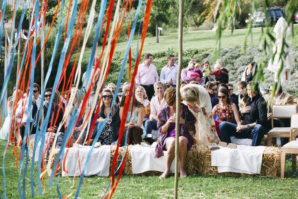 destination wedding in suedafrika: die Gäste sitzen während der Trauung auf Heuballen.